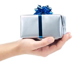 Silver gift box with blue ribbon on hand. This file contains clipping path.